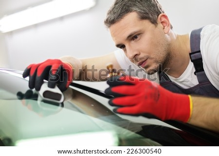 Worker on a car wash applying anti rain coating on a windshield  - stock photo