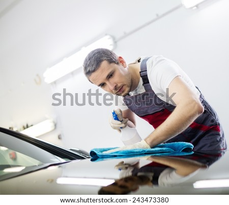 Worker on a car wash cleaning car with a spray - stock photo