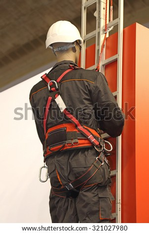 Worker on a Ladder Uses a Safety Harness to Prevent Falling From Building - stock photo
