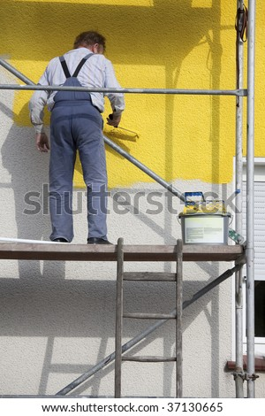 worker on a scaffold painting house with roller - stock photo