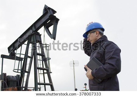 worker on an oil pump keeps the helmet with his hand