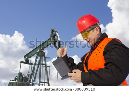 worker on an oil pump looking at lap top