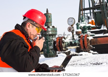 worker on an oil pump looks at laptop and speaking in a radio station,best focus Slam, right hand, laptop, glasses,Soft focus manometer,pump