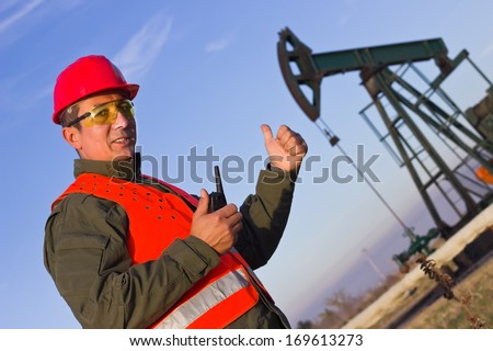 worker on an oil rig elevated thumbs, best focus vest, clothes and head man, pump soft focus