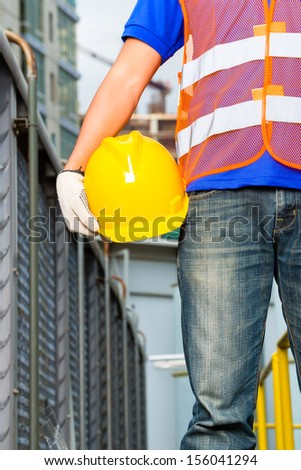 Worker on construction site with helmet or hard hat - stock photo