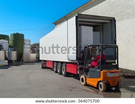 Worker on loader loads white semi-truck  - stock photo