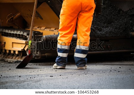 Worker on road construction, new asphalt - stock photo