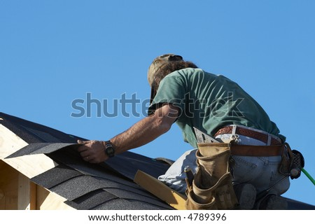worker on roof putting shingles down - stock photo