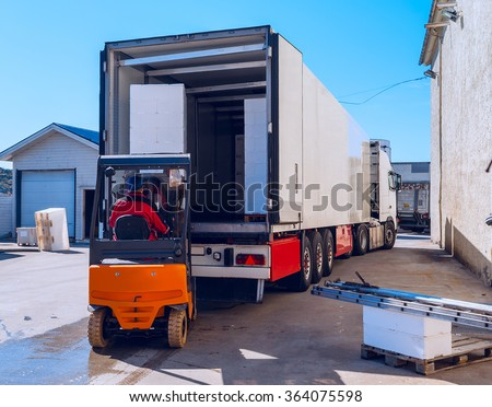 Worker on the loader loads long white semi-trailer  - stock photo