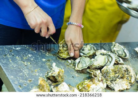 worker opening oysters at oyster farm or restaurant - stock photo
