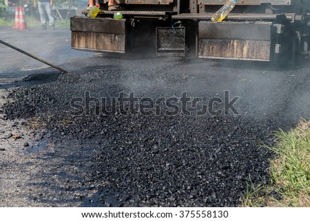 Worker operating asphalt paver machine during road construction and repairing works focus on asphalt road - stock photo