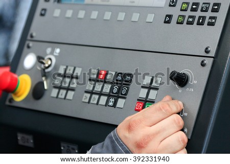 Worker operating the controls of CNC machine center. - stock photo