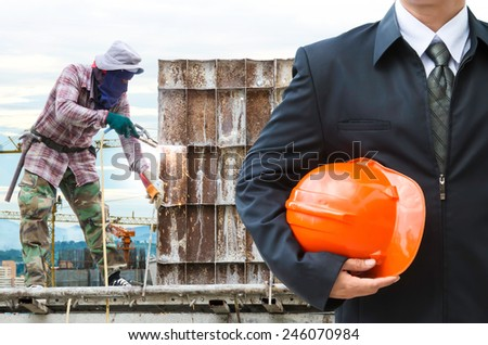 worker or engineer holding in hands orange helmet for workers security on the background of welding steel for structures roof at workplace  - stock photo