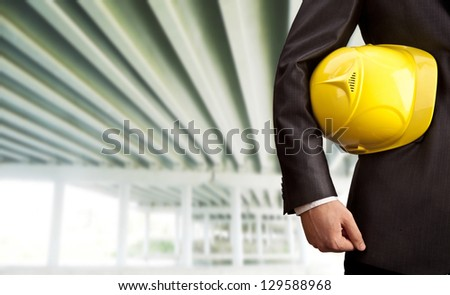 worker or engineer holding in hands yellow helmet for workers security on the background of a new  concrete bridge over the river  in perspective  buildings gray idea ??building new road junctions - stock photo