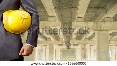 worker or engineer holding in hands yellow helmet for workers security on the background of a new concrete bridge over the river in perspective buildings gray idea   building new road junctions - stock photo