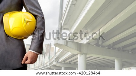 worker or engineer holding in hands yellow helmet for workers security on the background of a new concrete bridge over the highway in perspective buildings gray idea of building new road junctions - stock photo