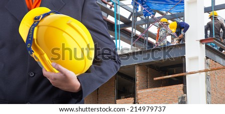 worker or engineer holding in hands yellow helmet for workers security on the background of welding steel for structures roof at workplace