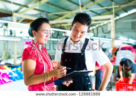 Worker or foreman and dressmaker or designer looking on Clipboard in a factory - stock photo
