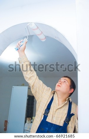 worker paint the arc, make renovation indoor. - stock photo