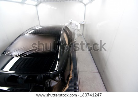 worker painting a black car in a special booth wearing protection gear