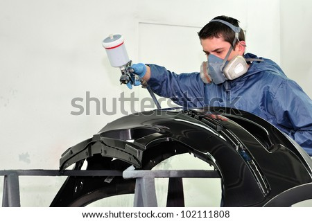 Worker painting a black fender.