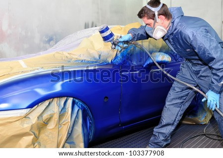 Worker painting a car in a paint booth, - stock photo