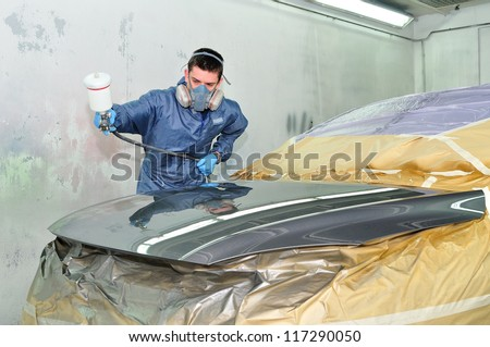 Worker painting a car in paint booth. - stock photo