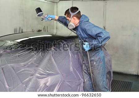 Worker painting a car roof. - stock photo