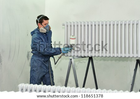 Worker painting a radiator in white. - stock photo
