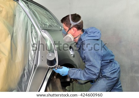 Worker painting a silver car. - stock photo