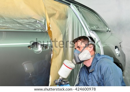 Worker painting a silver car.