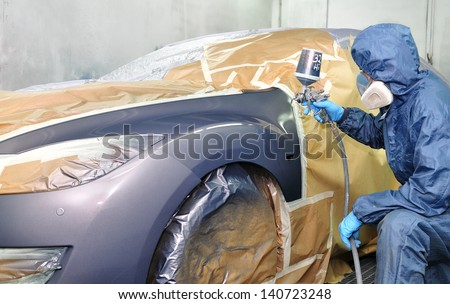 Worker painting car in a paint booth. - stock photo