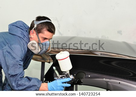 Worker painting car parts in a paint booth. - stock photo
