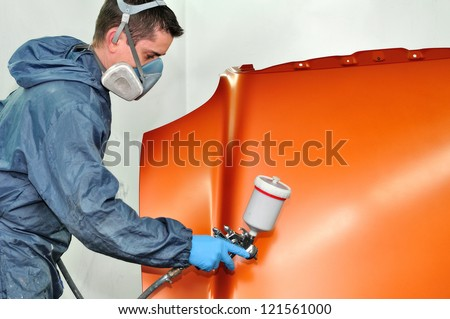 Worker painting orange bonnet. - stock photo