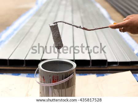 Worker painting steel bars with paint roller on construction site - stock photo