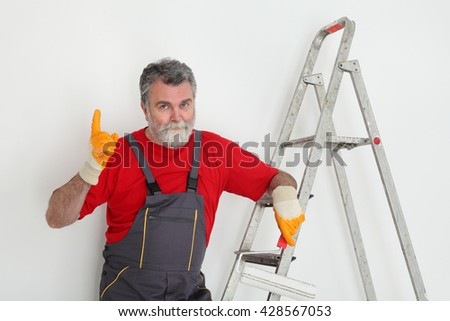 Worker painting wall to white and gesturing, with ladder and paint roller