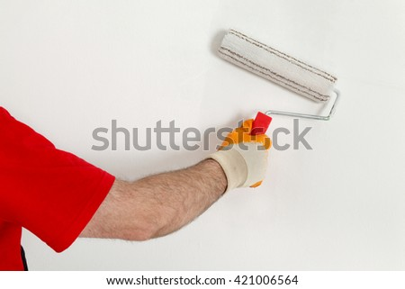 Worker painting wall to white with paint roller - stock photo