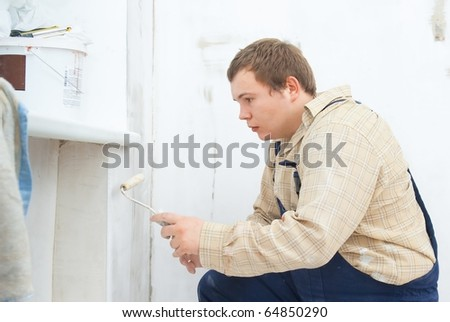 worker painting wall with roller - stock photo
