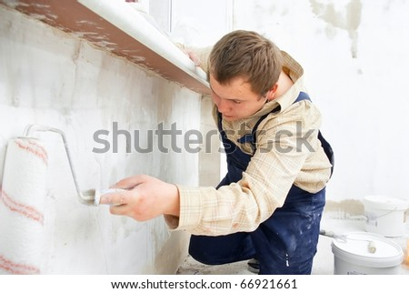 worker painting wall with roller