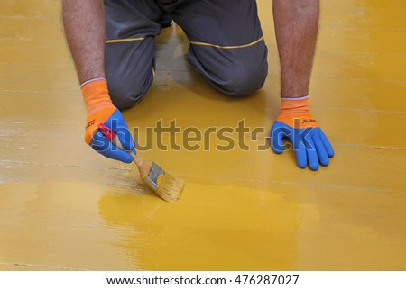Worker painting wooden floor to yellow