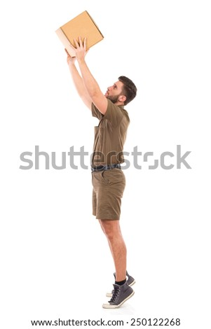 Worker picking up a package. Delivery man in khaki uniform picking up a carton box. Full length studio shot isolated on white. - stock photo