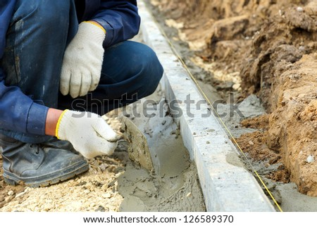 Worker placed curbs, close-up photos. - stock photo