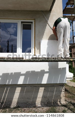 Worker placing styrofoam sheet insulation to the wall - stock photo
