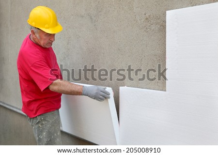 Worker placing styrofoam sheet insulation to wall at construction site - stock photo