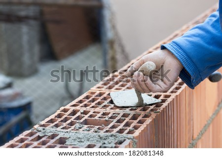 Worker plastering and layering wall bricks in shallow depth of field.