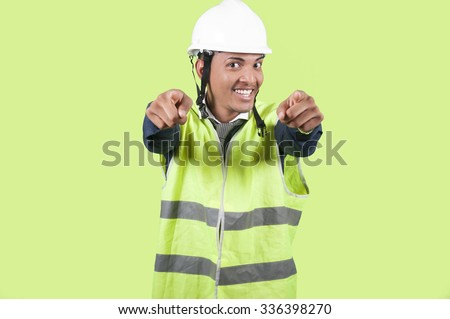 Worker pointing on green background - stock photo
