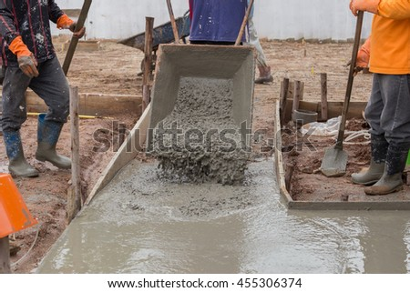 worker pouring cement from cart to floor at construction site