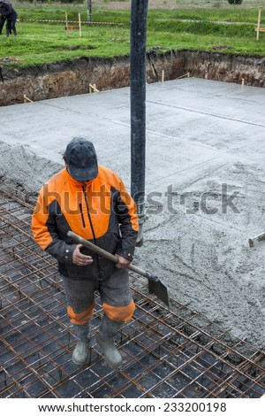 Worker pouring concrete mix into reinforced structure at the building site. - stock photo