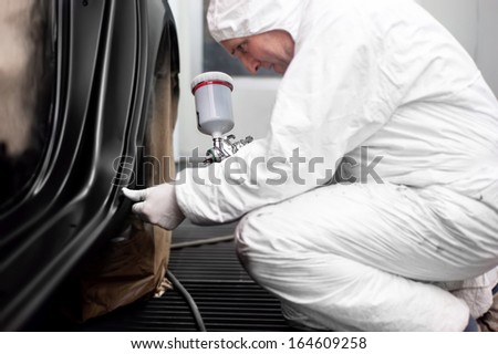 Worker preparing black paint for body work on a car wearing white special suit - stock photo