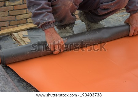 Worker preparing insulation material for basement wall, protection and drainage of walls and foundations - stock photo